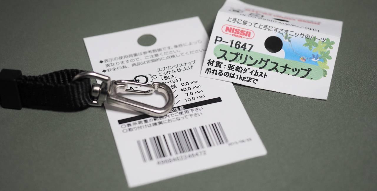 カラビナを付けたネックストラップと製品情報のイメージ。